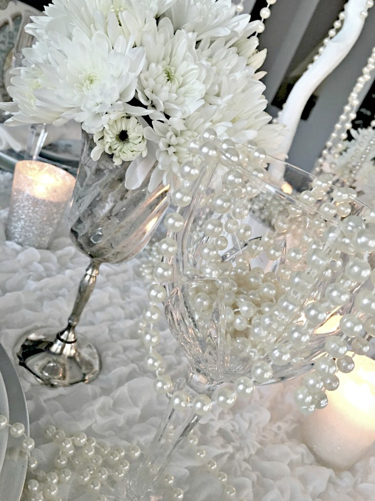 Stemware of silver and crystal with white flowers and white pearls set the scene for a winter tablescape