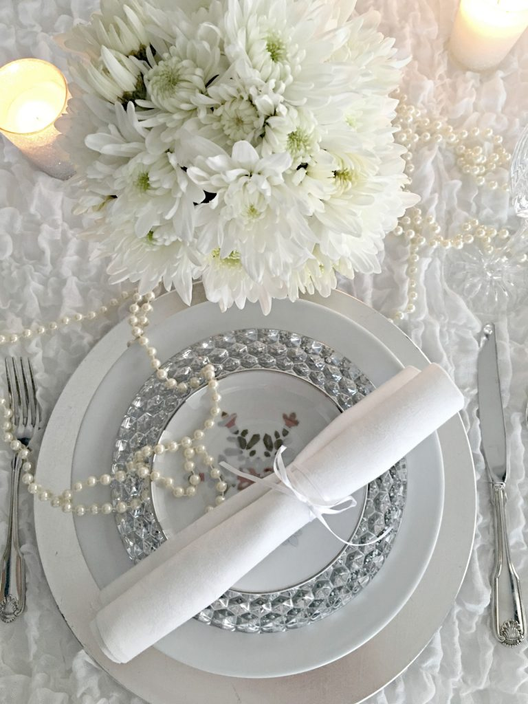 White and silver dishes with silver flatware and white mums adorn a winter white tablescape