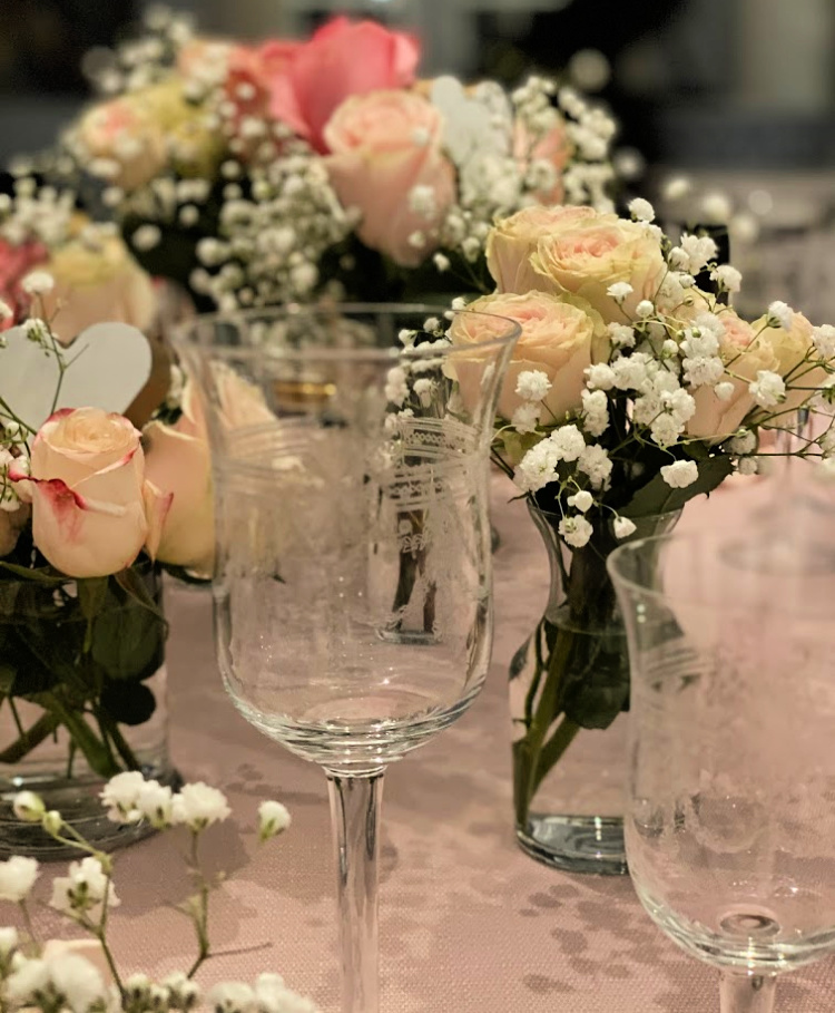 Delicate stemware with pink roses in vases behind them.