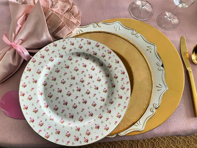 Floral plate, gold plates, white charger plates, gold charger plates and pink napkins