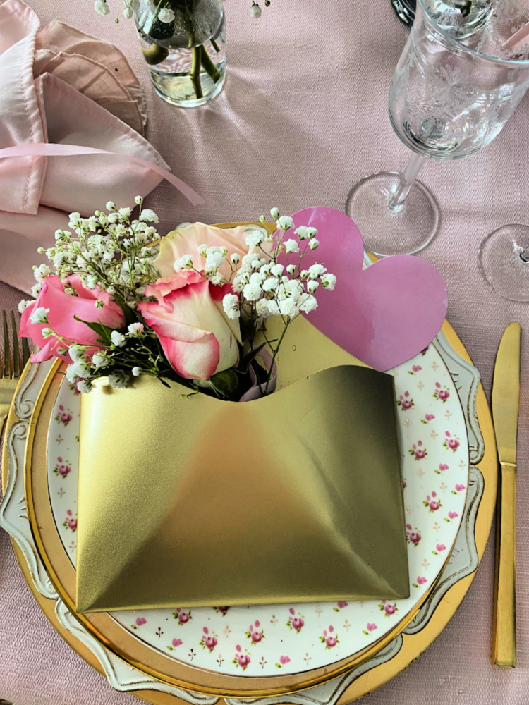 Valentine plate stack with a gold envelope filled with pink roses