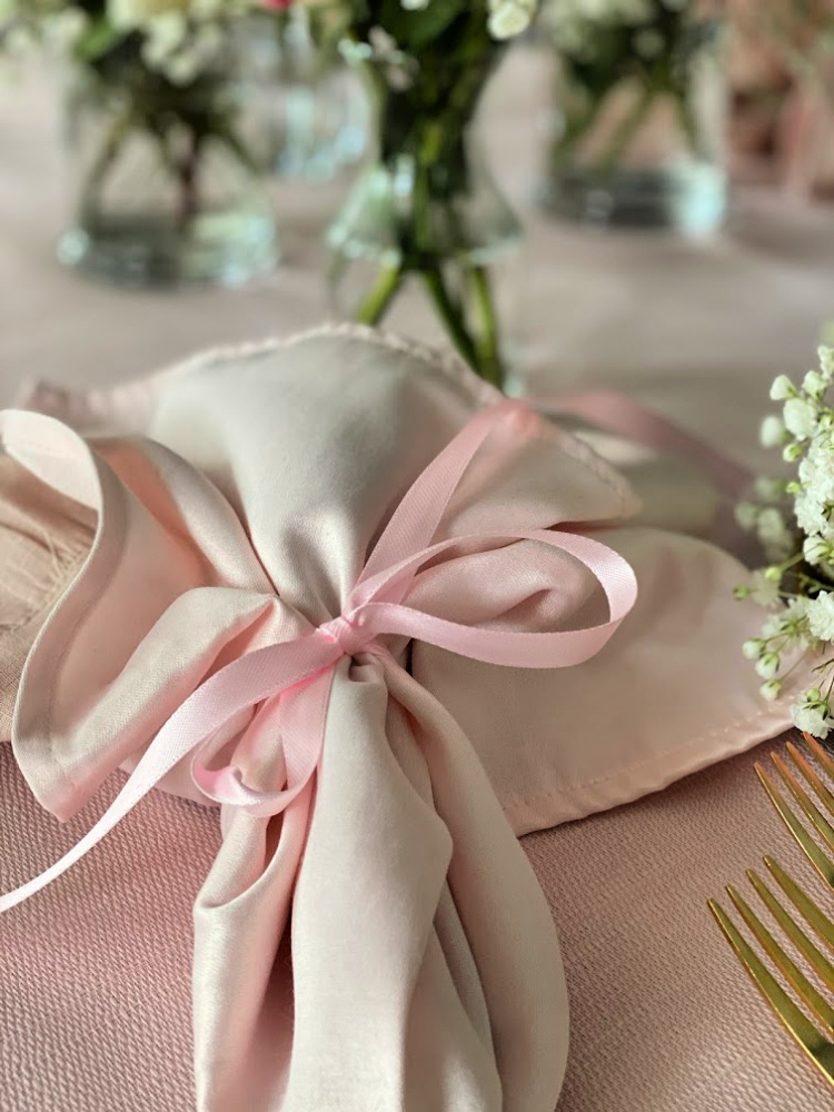Two pink napkins tied with a pink ribbon.