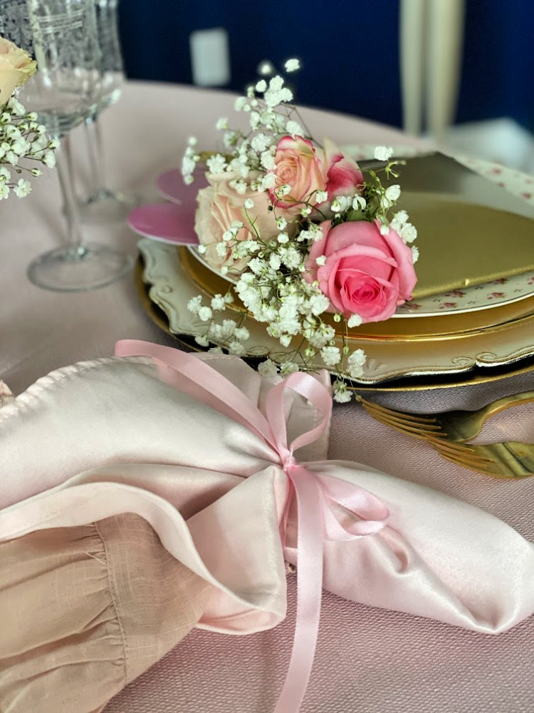 Two toned pink napkins tied with a pink ribbon and pink roses.