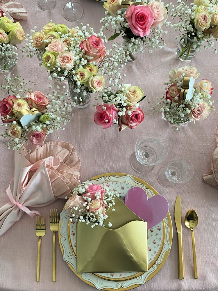 Vases of pink roses on a table along with a pretty valentine's place setting on a valentine tablescape