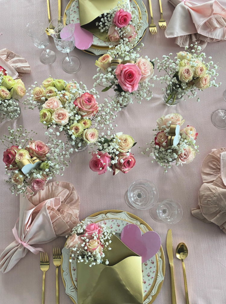 Vases of pink roses on a tabletop