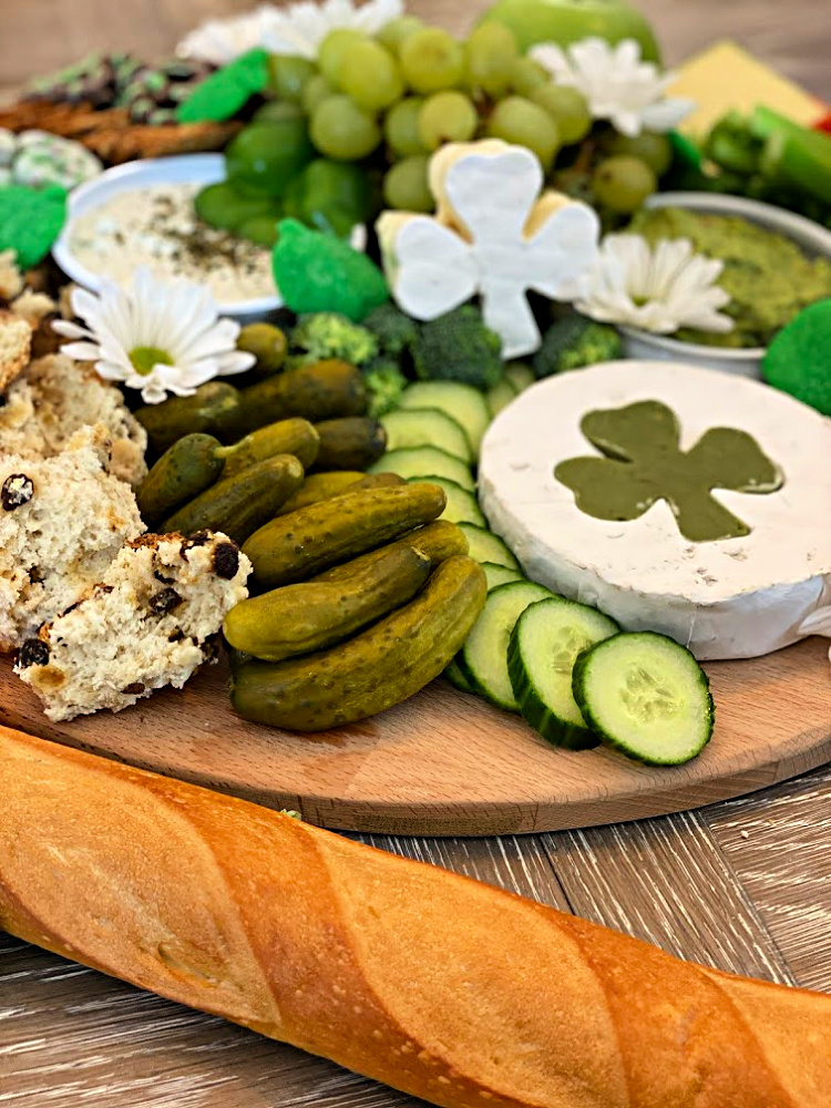 St. Patrick's Day grazing board with green foods and a shamrock shaped cheese