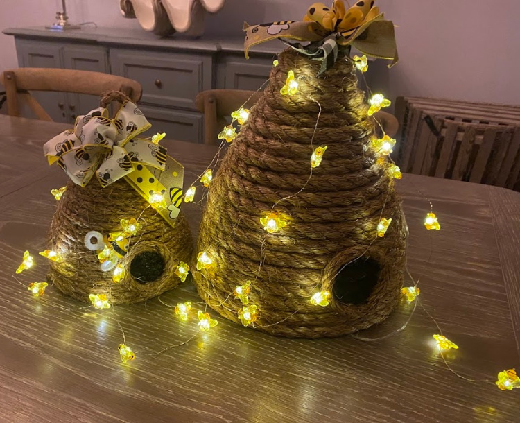 Two diy bee skeps made with jute rope and lit with battery operated little bee lights