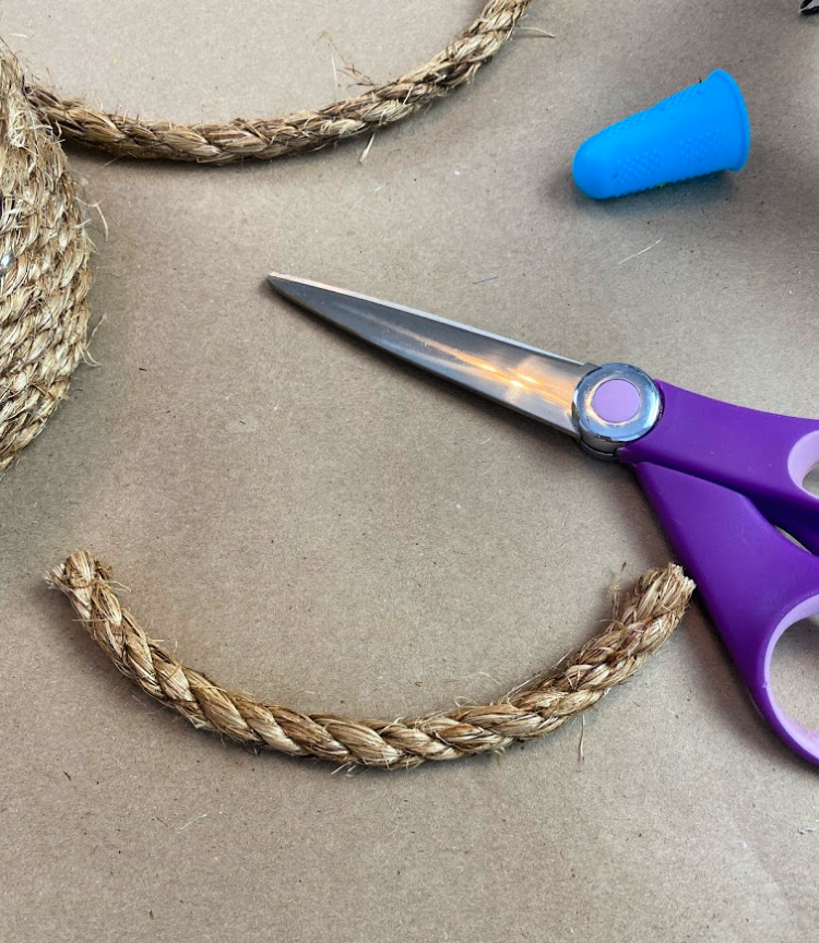 purple handled scissors, a piece of jute rope and a silicone finger protector