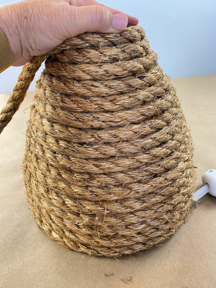 A jute rope coiled bee skep with a hand on the top of it