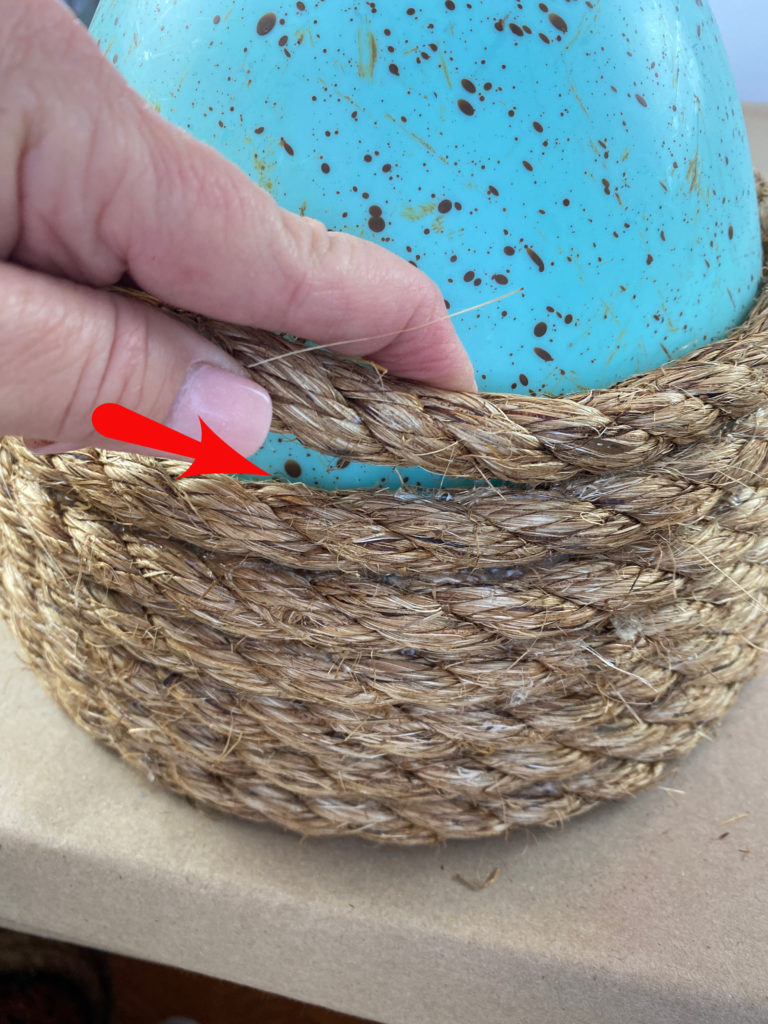 A blue decorative easter egg with jute rope being glued around it.  a red arrow and a hand wrapping the rope around the egg.