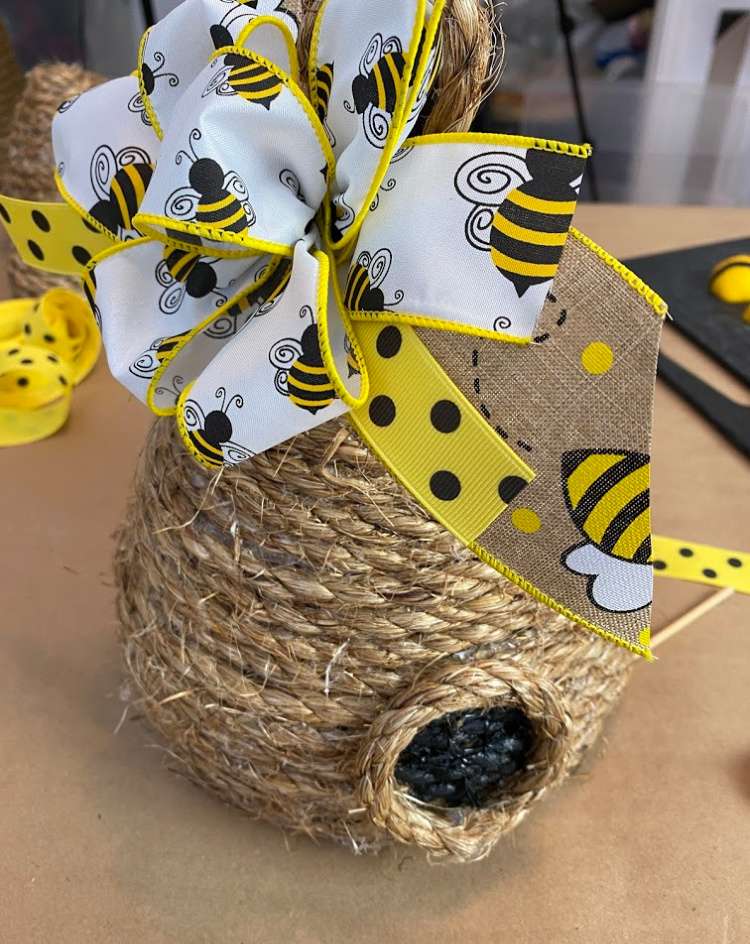 One decorative bee skep made with jute rope with a cute bee themed ribbon tied in a bow on the top.