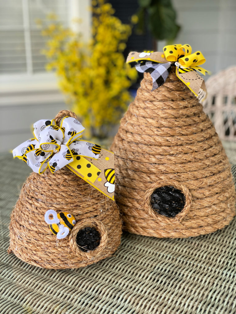 Two diy bee skeps made from jute rope and trimmed with bee themed ribbons