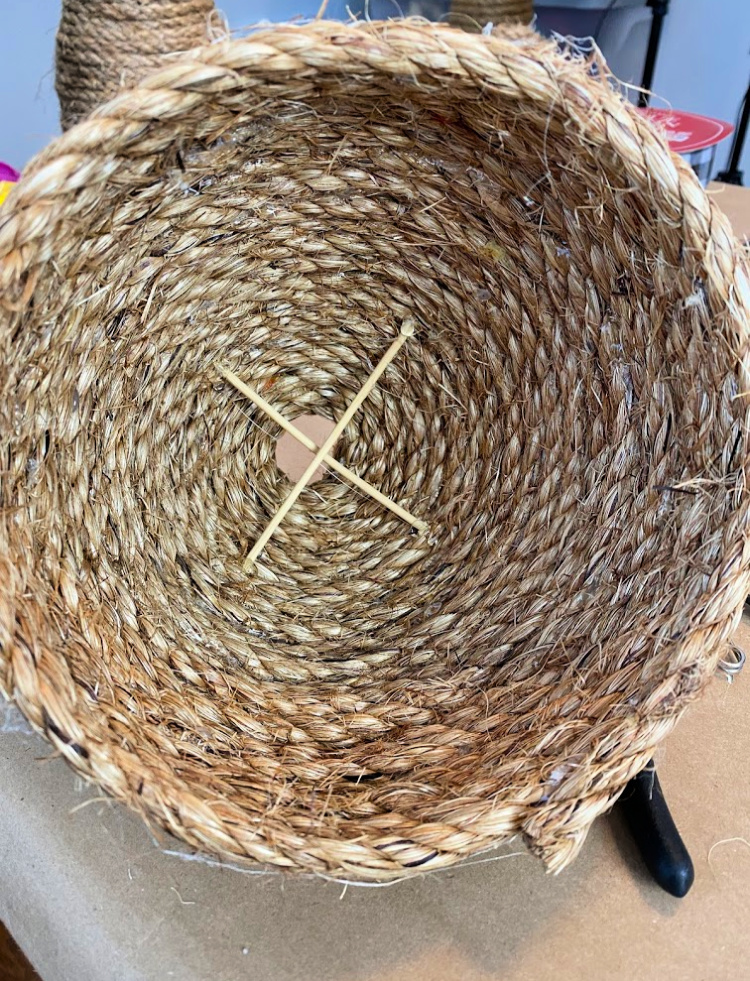 View inside of a decorative rope bee skep with two wood dowels crossed up inside of it