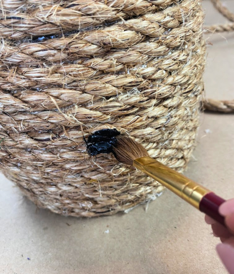 paintbrush painting a black spot on a jute decorative bee skep