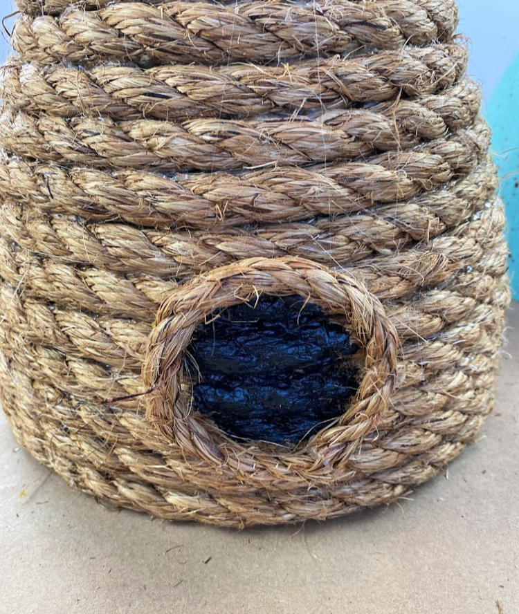 """a decorative bee skep made with jute rope with a painted black circle on it for a """"door"""""""