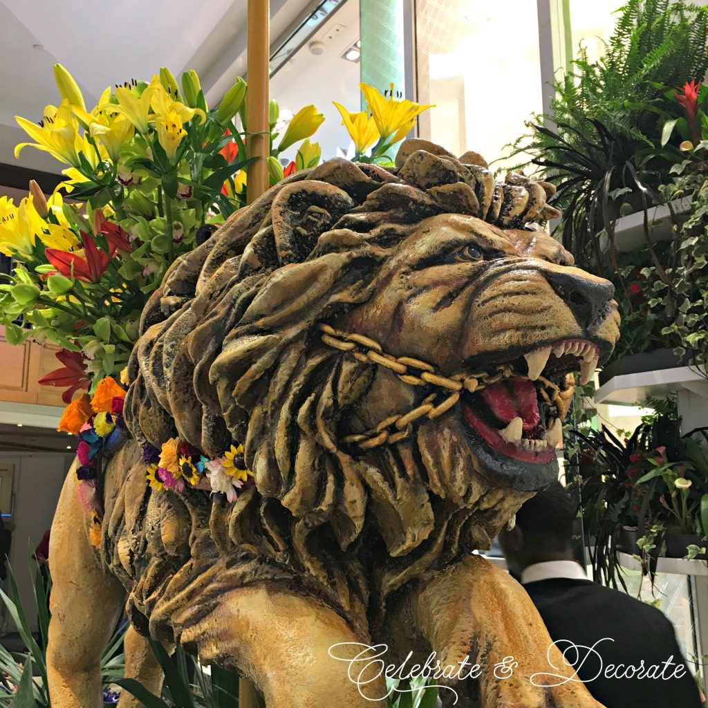 A lion carousel animal is decked out with fresh flowers