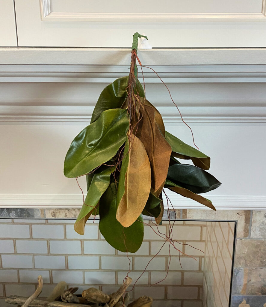 cluster of magnolia leaves hanging from a mantel