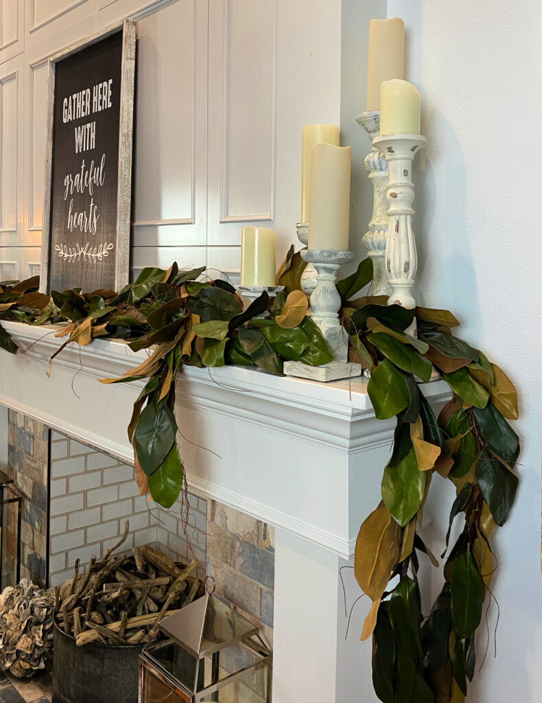 white mantel with white candlesticks on it and magnolia leaves