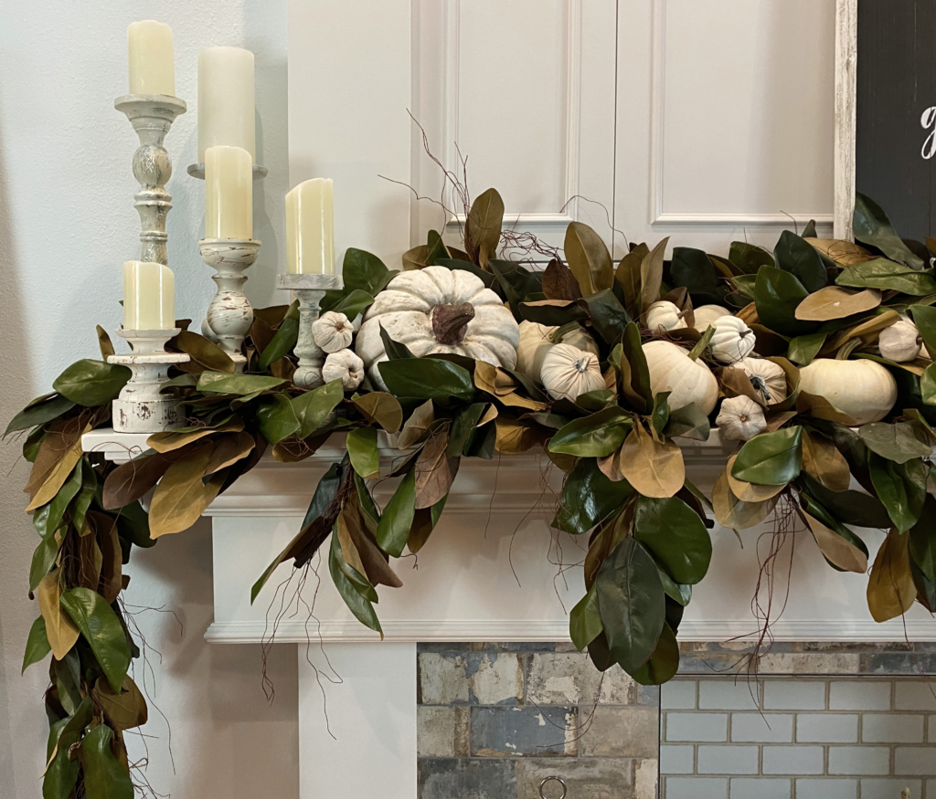 black and white sign on white mantel with magnolia garlands and white pumpkins