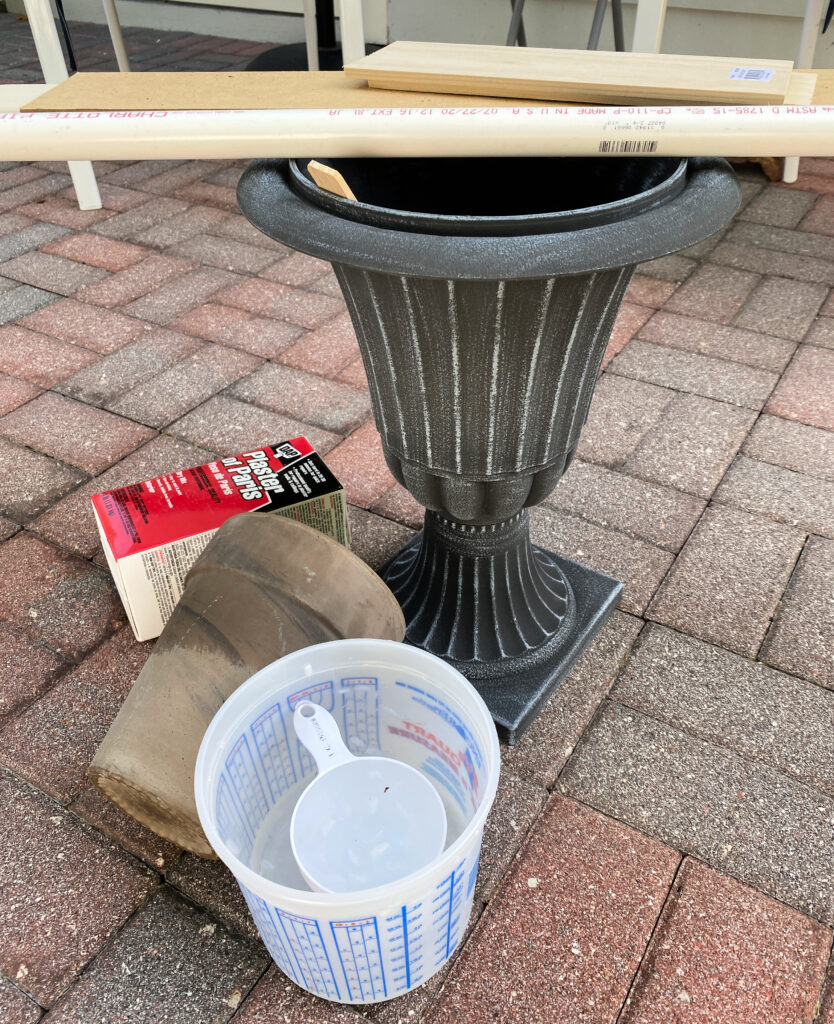 picture of a brick patio with a grey urn planter, a brown flower pot, a box of plaster of paris, a piece of pvc pipe, some boards, and a mixing container and a measuring cup