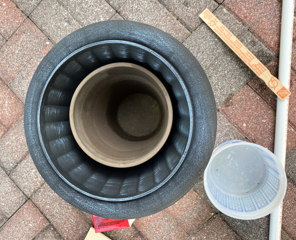 overhead hot of a gray urn planter with a brown flower pot sitting in it on a brick patio.  a piece of white pvc pipe sitting on the ground, a paint stirrer, a paint mixing bucket