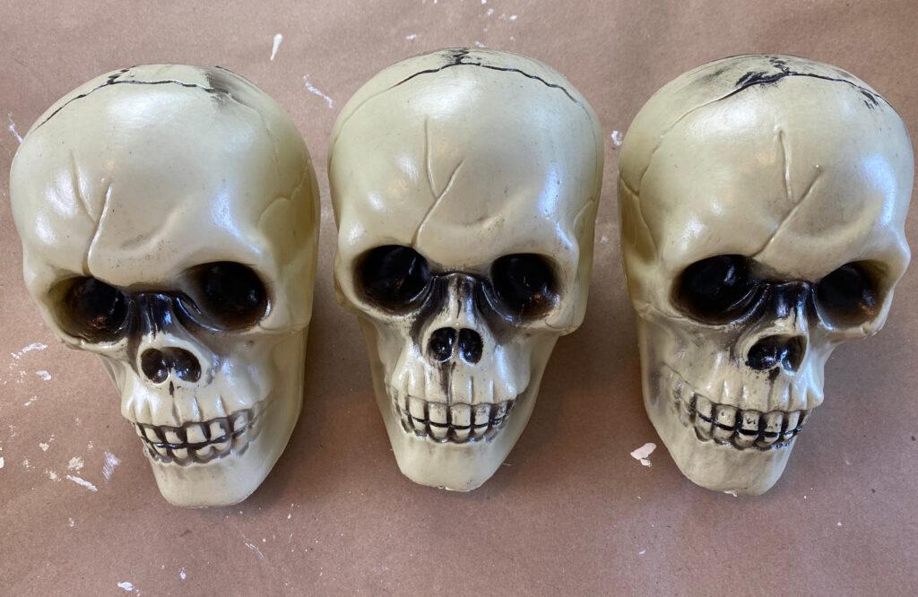 three dollar store plastic skulls sitting on brown paper