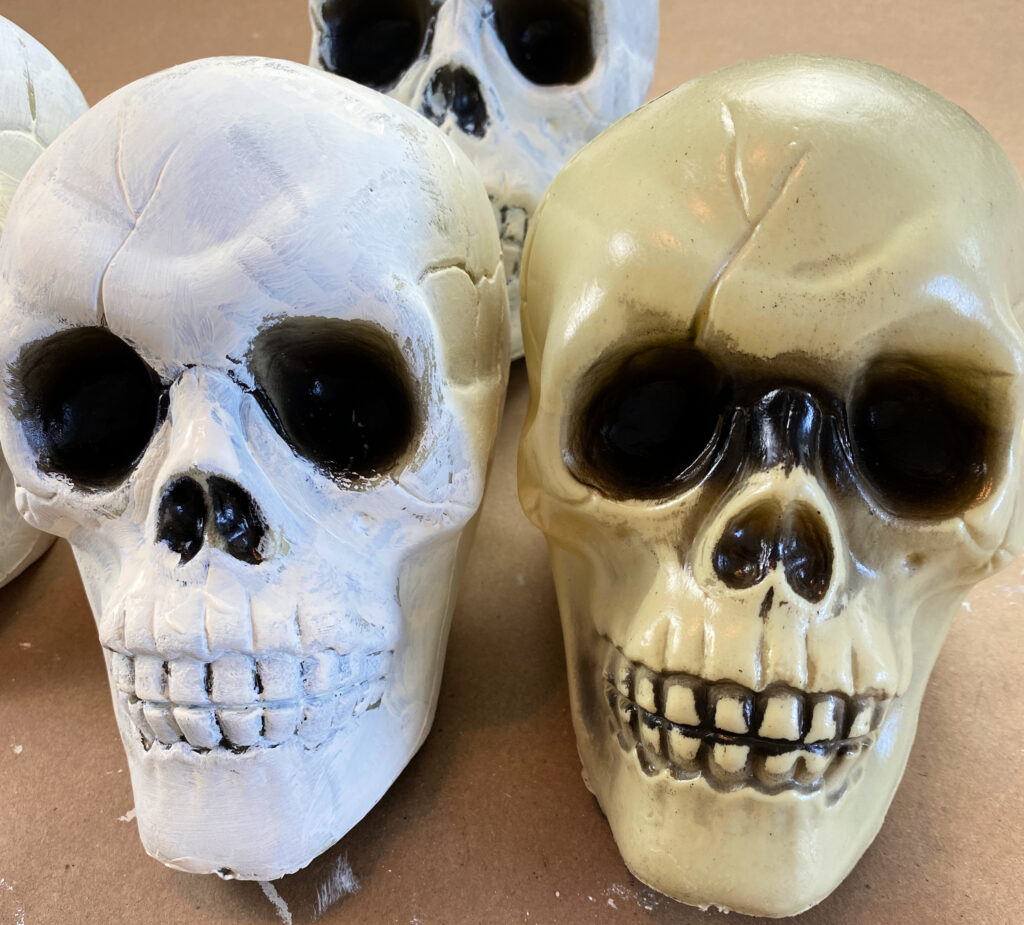 three dollar store plastic skulls, two painted white, one natural