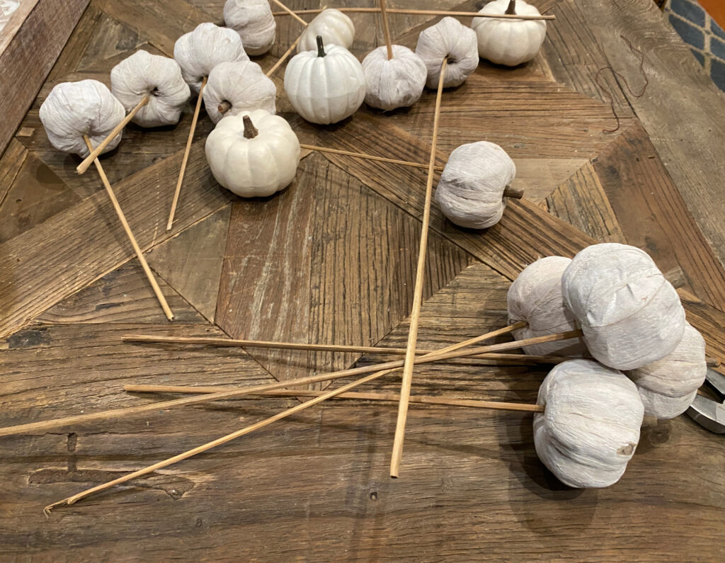 small white faux pumpkins with skewers in them