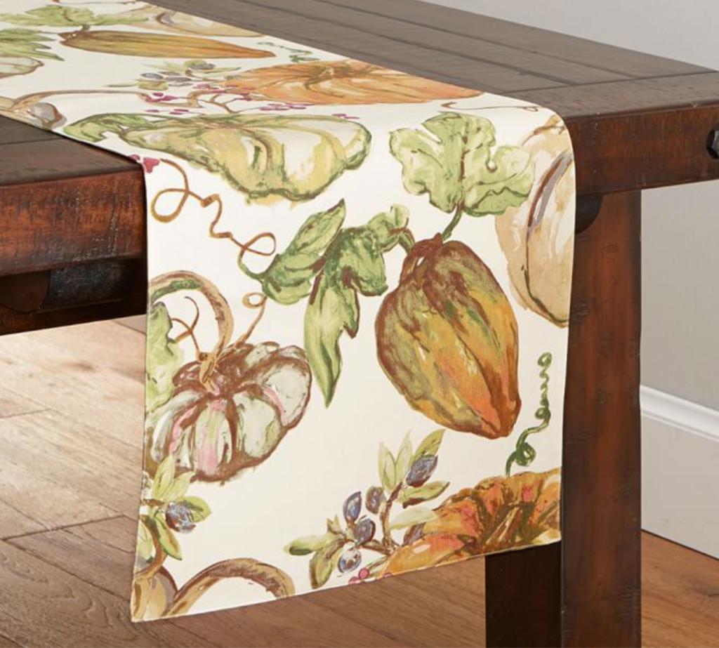 Elegant fall pumpkin table runner on wood table
