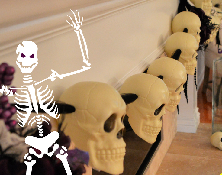 picture of plastic halloween skulls made into a garland hanging from a mantel.