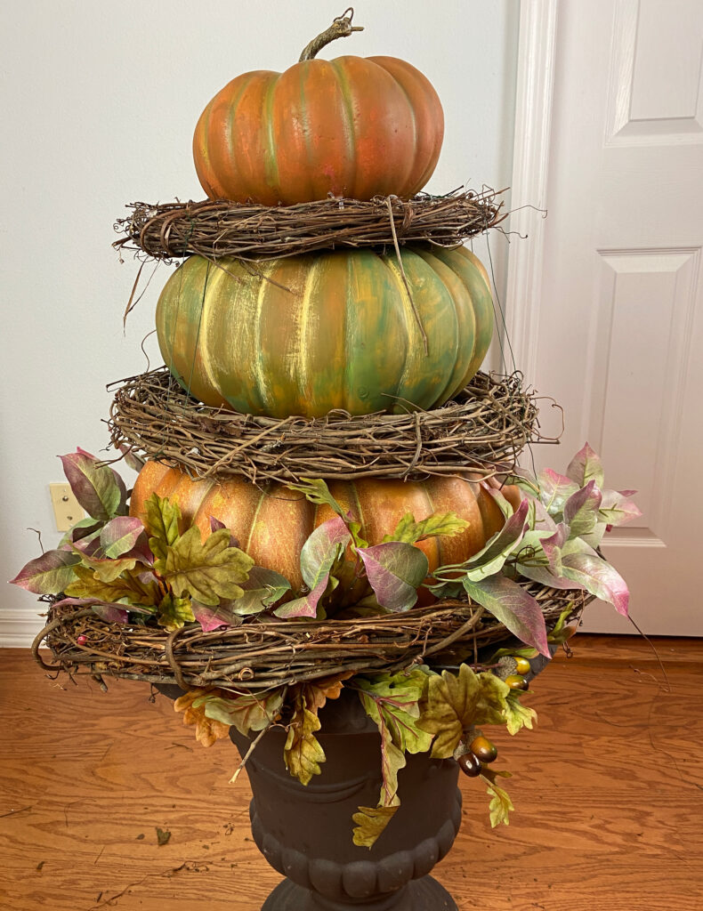 Stacked pumpkins with grapevine wreaths.