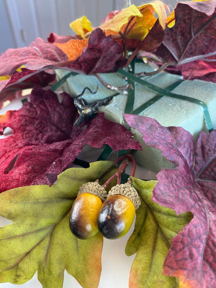 faux fall leaves and acorns being stuck into dry floral foam