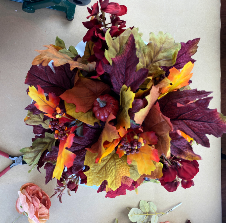 overhead view of faux floral leaves in a pumpkin
