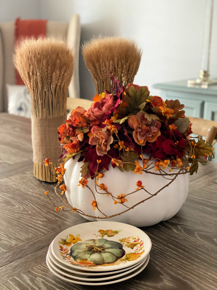 White pumpkin with fall floral arrangement with a pair of white bundles and a stack of pumpkin plates on a table