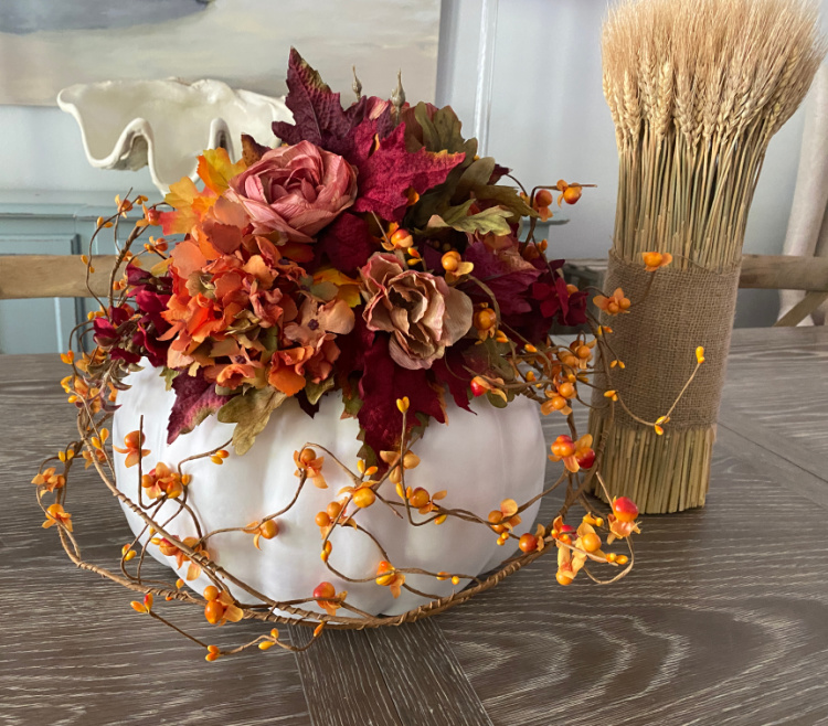 White pumpkin with fall floral arrangement on a table with a bundle of wheat