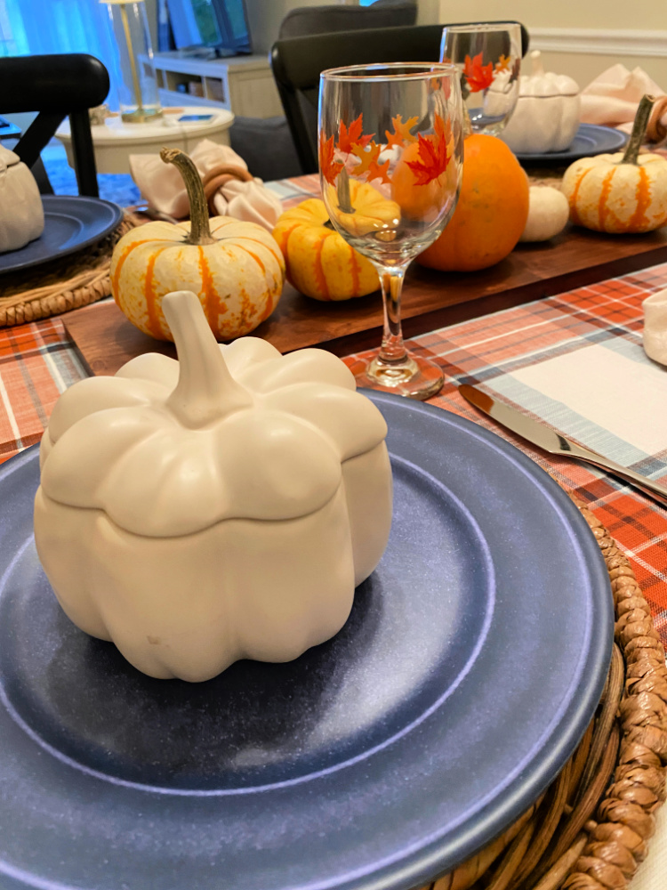 a plaid fall tablecloth, a long wood cutting board with tiny pumpkins on it.  a blue plate on a wicker placemat and a white pumpkin soup tureen on the blue plate.  a wine glass with orange fall leaves on it