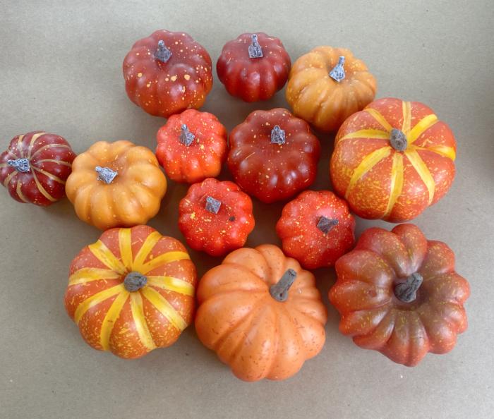 13 miscellaneous small orange craft pumpkins arranged on kraft paper