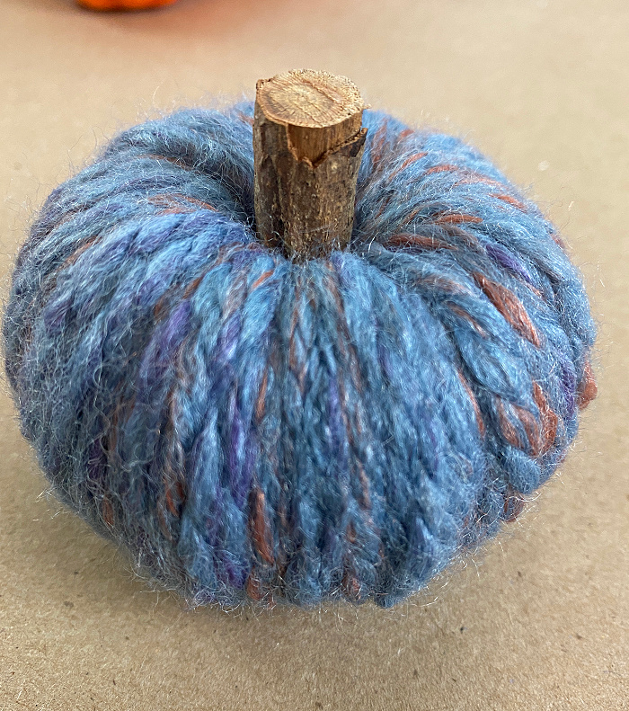 tiny blue and rust yarn wrapped faux pumpkin with a twig stem