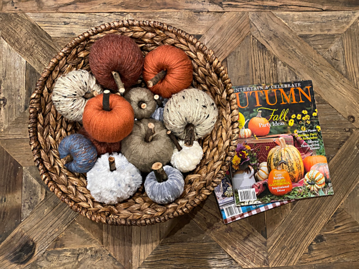 basket of yarn wrapped tiny faux pumpkins on a wooden tabletop with a couple of autumn magazines next to it