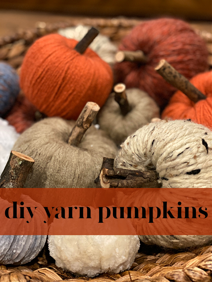 close up photo of yarn wrapped pumpkins in browns and shades of orange and browns with little stems made from twigs with a title in orange over the picture that says diy yarn pumpkins