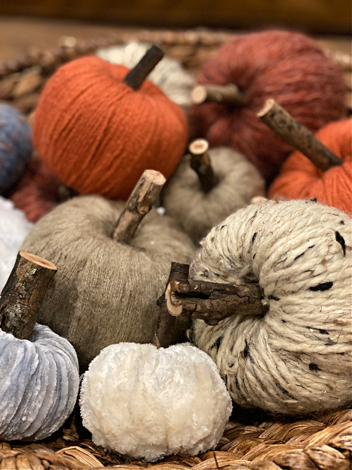 close up of some mini yarn wrapped faux pumpkins in fall colors with twig stems