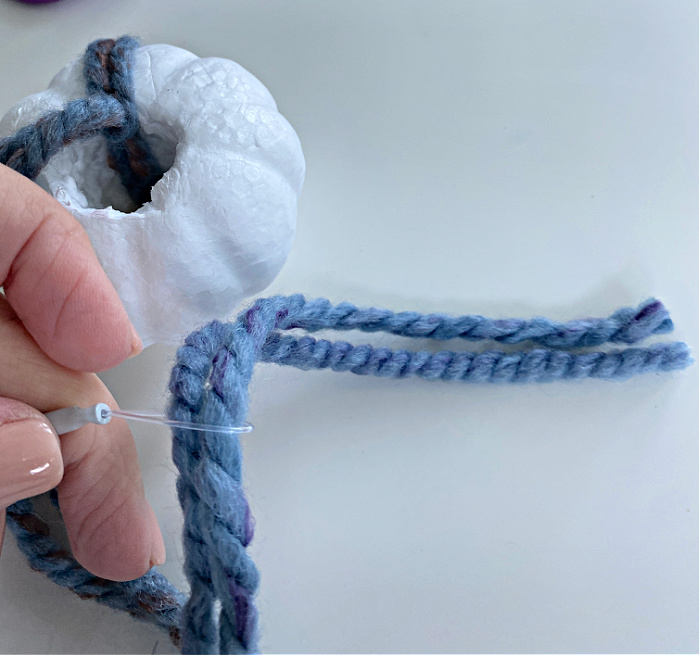 fingers holding a wool needle with double strands of blue yarn threaded through it and a white styrofoam pumpkin with a couple of strands of the blue yarn wrapped around it