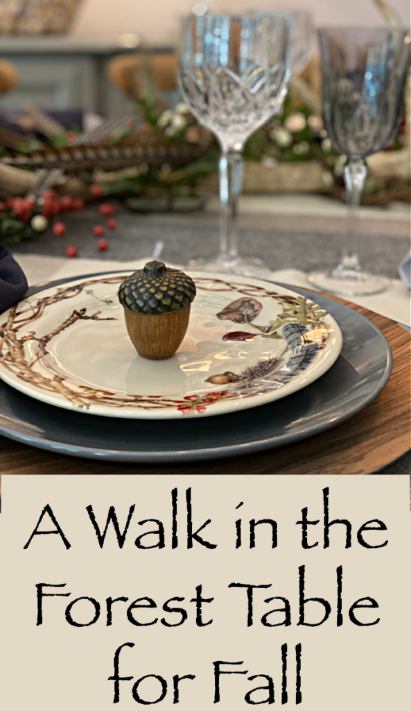 A title page that says a Walk in the Forest Table for Fall, a fall place setting with a gray dinner plate with a decorative salad plate and a tiny acorn candle,  crystal water goblet and a gray wine glass and in the background a centerpiece.