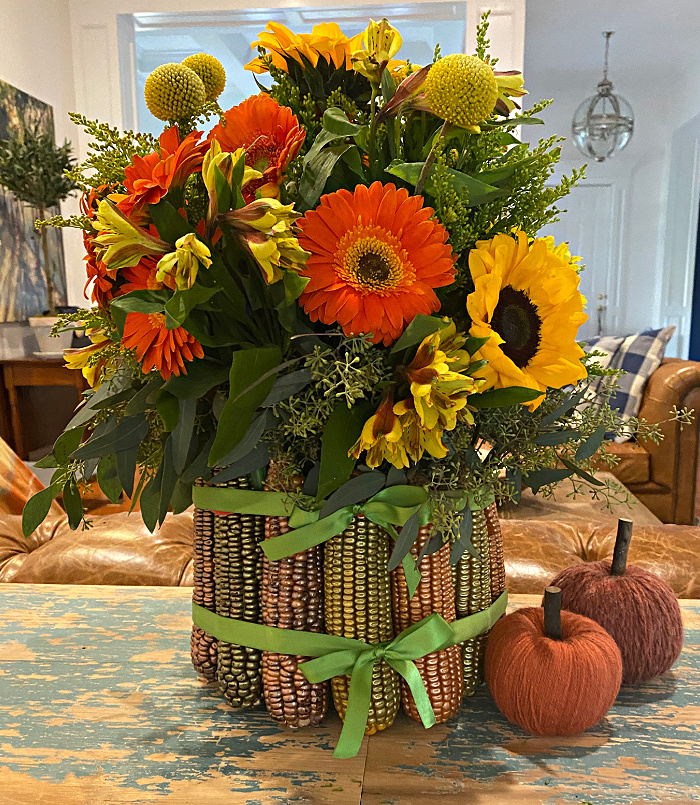 Floral arrangement of oranges and yellows in a vase of metallic painted corn cobs tied with green ribbon and two little pumpkins wrapped in yarn set in a living room