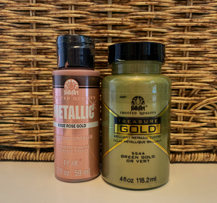 two jars of paint, rose gold and green gold metallic sitting in front of a wicker basket