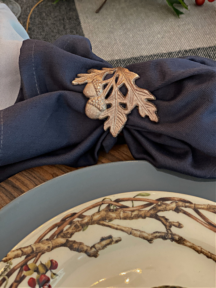 Slate blue and gray napkins layered and tucked inside a brass oak leaf and acorn napkin ring set next to a gray dinner plate and topped with a cream color salad plate with branches on it.