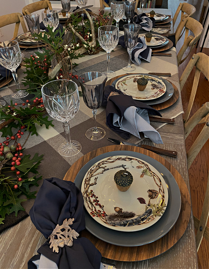A table set for eight for fall with a plaid throw for a tablecloth, wooden chargers, gray dinner plates and decorative salad plates, wooden handled flatware and crystal goblets and a centerpiece of antlers, oak leaves, and pheasant feathers and layered napkins of slate blue and gray layered napkins.