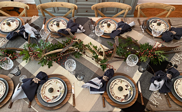 A table set for eight for fall with a plaid throw for a tablecloth, wooden chargers, gray dinner plates and decorative salad plates, wooden handled flatware and crystal goblets and a centerpiece of antlers, oak leaves, and pheasant feathers