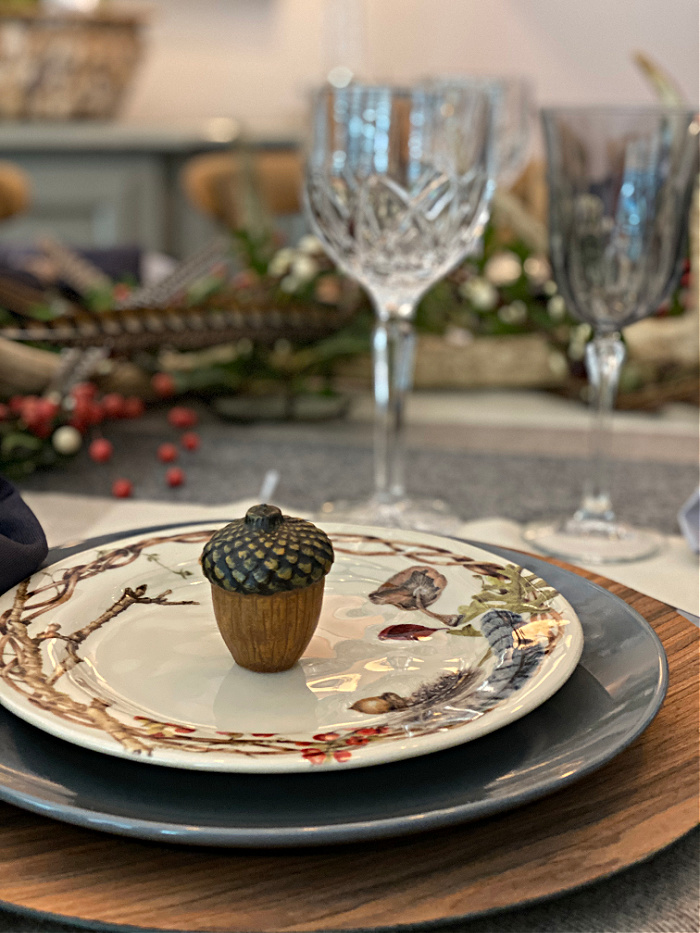 A place setting a faux wood charger, a gray dinner plate topped with a salad plate that is cream color with branches around the edges also decorated with berries, acorns, feathers and fungi with an acorn candle set on the salad plate.  Crystal  water and wine glasses in the background along with the natural looking centerpiece of oak leaves, berries and pheasant feathers.