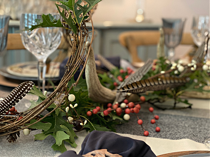 Part of a centerpiece of grapevines, oak leaves, feathers, an antler and berries along with the crystal glasses on a tabletop